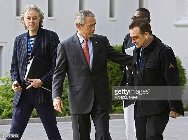 President George W Bush walks with Irish environmental activist and U2 lead singer Bono Irish political activist Bob Geldof and Senegalese musician...