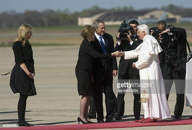 US President George W Bush watches as First Lady Laura Bush shakes hands with Pope Benedict XVI upon the Pope's arrival at Andrews Air Force Base in...