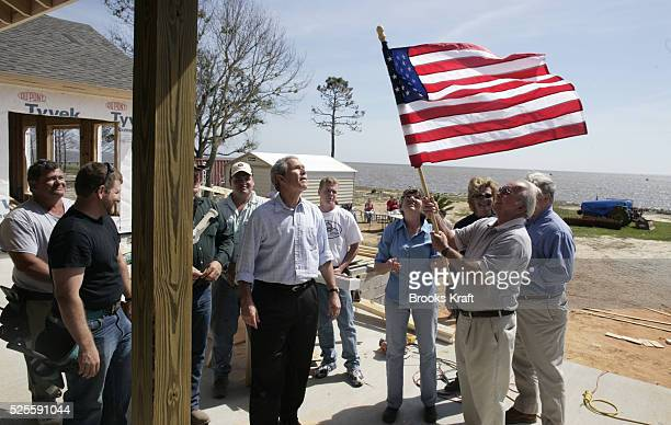 US President George W Bush watches as homeowner Jerry Akins places a flag on his home as Mississippi Governor Haley Barbour and his wife Marsha look...