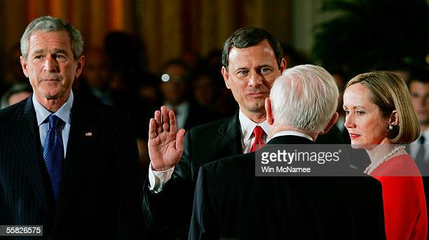 S President George W Bush watches as John Roberts is sworn in as Chief Justice of the United States Supreme Court by Associate Justice John Paul...