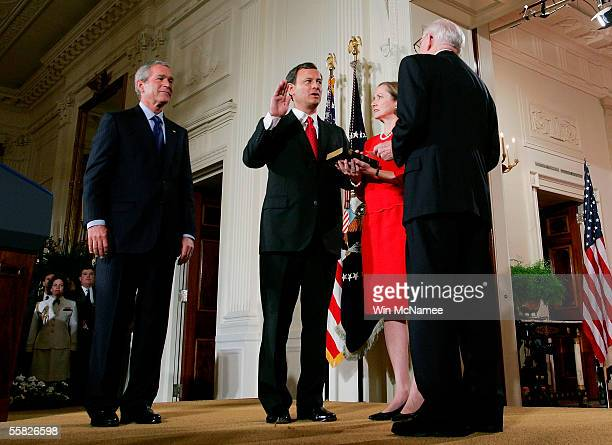 President George W. Bush watches as John Roberts is sworn in as Chief Justice of the United States Supreme Court by Associate Justice John Paul...