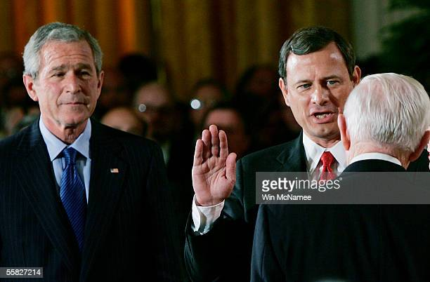 President George W. Bush watches as John Roberts is sworn in as chief justice of the U.S. Supreme Court by Associate Justice John Paul Stevens during...