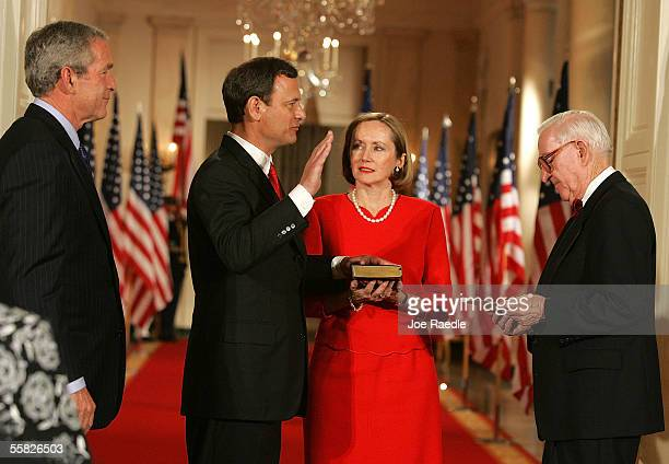 President George W. Bush watches while John Roberts is sworn in as Chief Justice of the U.S. By Associate Justice John Paul Stevens as Roberts' wife,...