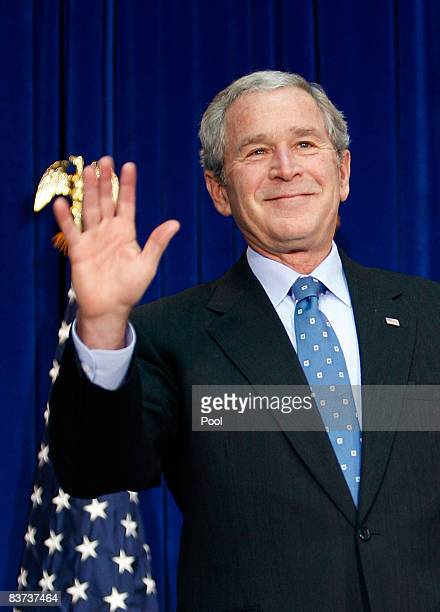 US President George W Bush waves after speaking on aviation congestion and transportation safety at the US Department of Transportation on November...