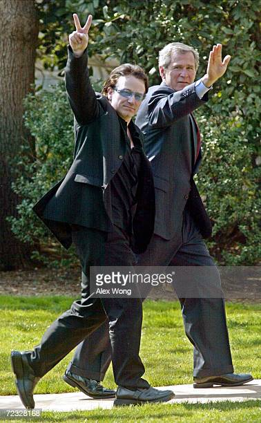 S President George W Bush waves as Bono the lead singer of Irish pop group U2 makes a V sign as they walk toward the Oval Office of the White House...
