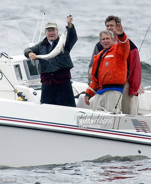 US President George W Bush waves as he fishes with his father former US President George Bush and his brother Marvin Bush 15 June 2003 in...