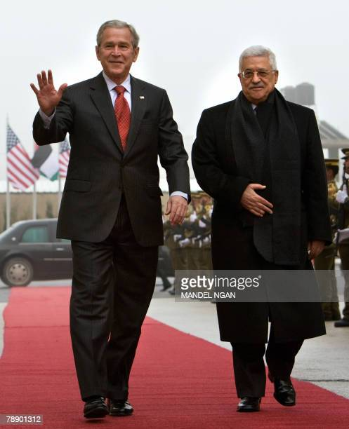 President George W. Bush waves as he walks alongside Palestinian leader Mahmud Abbas, during a ceremony at the Muqataa, the Palestinian Authority...