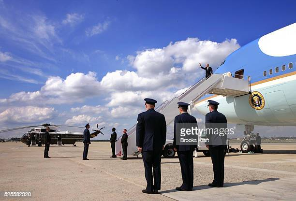 US President George W Bush waves as he walks off Air Force One at Andrews Air Force Base after returning from the G8 Summit in Scotland July 8 2005