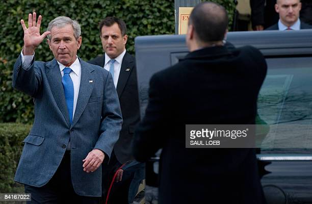 US President George W Bush waves as he walks to his limousine surrounded by members of the US Secret Service after attending Sunday church services...