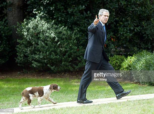 S President George W Bush waves as he walks toward the Oval Office with his dog Spot September 23 2002 in Washington DC Bush returned from a...