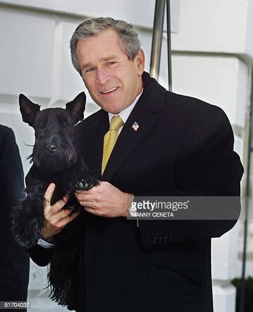 President George W Bush waves his pet dog Barney's foot as he was asked a question by a journalist at the White House after a trip from North...