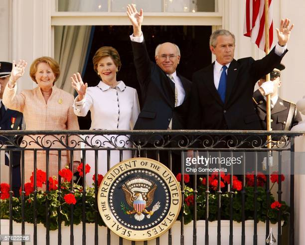 S President George W Bush waves with Australian Prime Minister John Howard first lady Laura Bush and Janette Howard as they stand on the Truman...