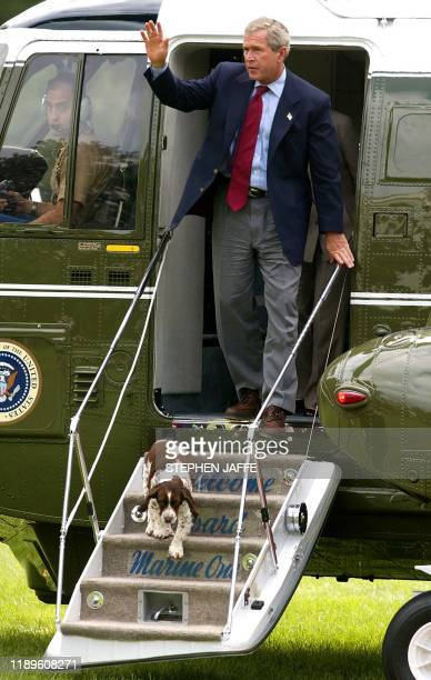 US President George W Bush waves with his dog Spot after arriving back at the White House 14 September 2003 in Washington DC Bush spent the weekend...