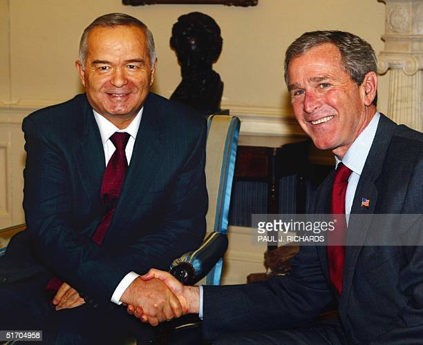 President George W Bush welcomes Uzebekistan President Islom Karimov to the Oval Office 12 March 2002 with a hand shake during a private meeting at...