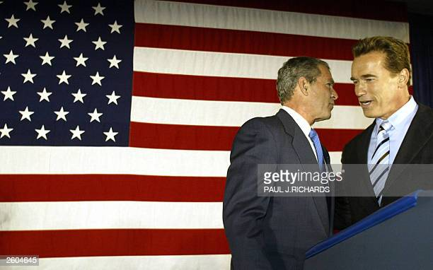 President George W Bush whispers to California governorelect Republican Arnold Schwarzenegger 16 October 2003 at the San BernardinoRadisson Hotel and...