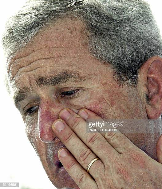 President George W. Bush wipes his face as he delivers remarks in a hot and humid New Port Richey, Florida, 19 October 2004 during a campaign rally....