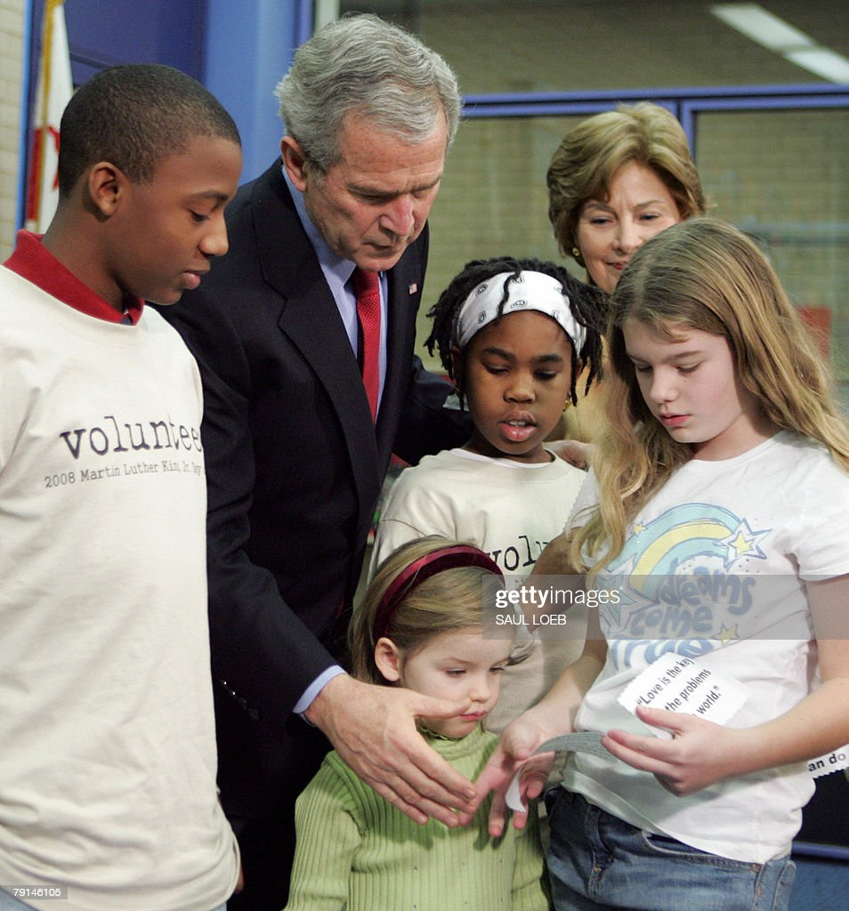 US President George W. Bush (2nd L), with First Lady Laura Bush (2nd R) participates in a lesson for young children on the importance of Martin Luther King, Jr. Day during a tour of the Martin Luther King, Jr. Memorial Library in Washington, DC, 21 January 2008.