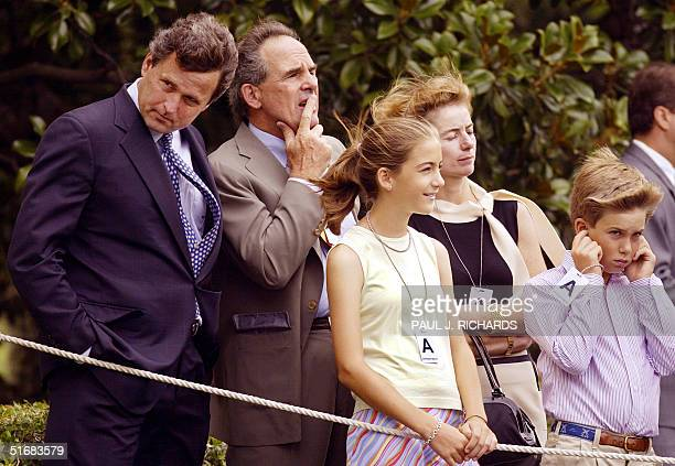 President George W Bush's brother Marvin stands with unidentified friends as his brother takes off on Marine One 22 July 2002 from the South Lawn of...