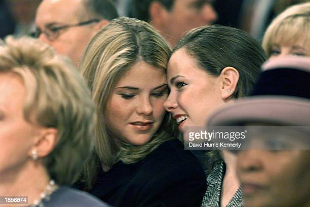 US President George W Bush's twin daughters Jenna and Barbara whisper during a preinaugural event January 19 2001 in Washington DC