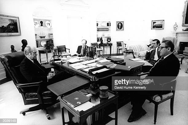 President Gerald Ford speaks with Chief of Staff Donald Rumsfeld and Henry Kissinger in his office in 1974 at the White House in Washington DC