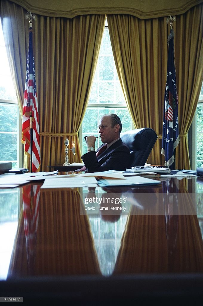 President Gerald R. Ford sits at his desk in the Oval Office on August 1974 in Washington, D.C. Ford stepped into office as president on August 9th, after the resignation of Richard M. Nixon.
