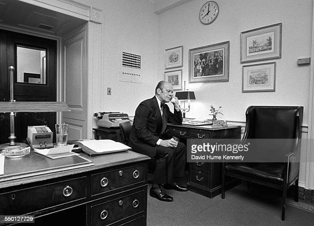 President Gerald R Ford takes a call from Defense Secretary James Schlesinger in the White House usher's office informing him that the evacuation of...