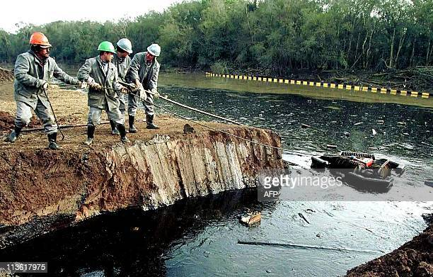 President Getulio Vargas refinery workers try to clean oil spilled in the Iguazu River in Curtiba Brazil 19 July 2000 Four million liters of crude...