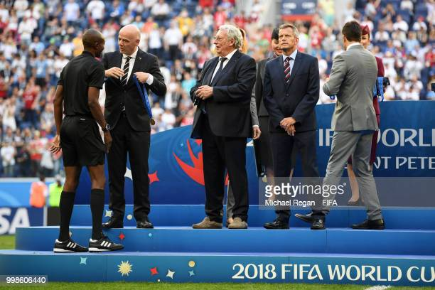 FIFA president Gianni Infantino awards Fourth official Malang Diedhiou during medal ceremony following the 2018 FIFA World Cup Russia 3rd Place...