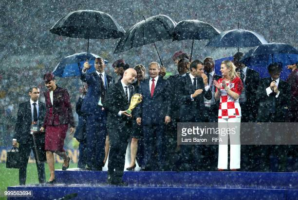FIFA president Gianni Infantino carries the World Cup trophy in front of President of Russia Vladimir Putin French President Emmanuel Macron and...