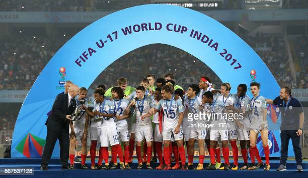 President Gianni Infantino delivers the champion trophy to the captain Angel Gomes of England after the FIFA U17 World Cup India 2017 Final match...