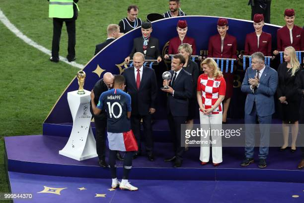 President Gianni Infantino greets Kylian Mbappe of France as French President Emmanuel Macron prepares to present him with the FIFA Young Player...