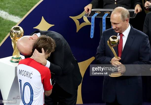 President Gianni Infantino greets Luka Modric of Croatia as President of the Russian Federation Vladimir Putin prepares to award him with his Golden...