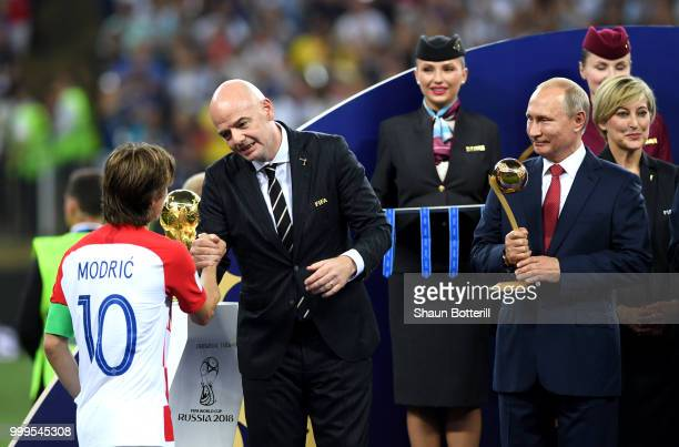 President Gianni Infantino greets Luka Modric of Croatia as President of Russia Vladimir Putin and French President Emmanuel Macron looks on during...