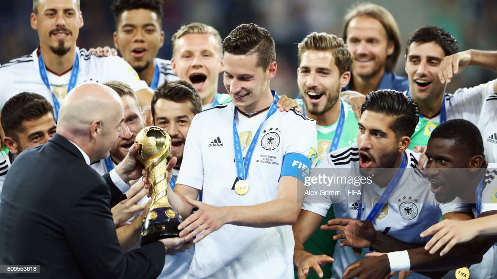 President Gianni Infantino hands over the trophy to team captain Julian Draxler of Germany after the FIFA Confederations Cup Russia 2017 final between Chile and Germany at Saint Petersburg Stadium on July 2, 2017 in Saint Petersburg, Russia.