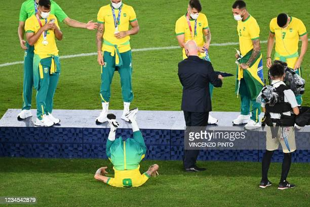 President Gianni Infantino looks as Brazil's gold medallist Guilherme Arana jokes as the team receive their medals on the podium during the medal...