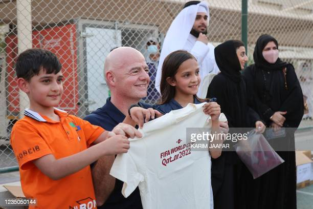President Gianni Infantino poses for a picture with Afghan refugees at their place of accommodation at Park View Villas, a Qatar's 2022 FIFA World...