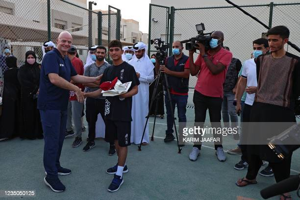 President Gianni Infantino poses for a picture with an Afghan refugee at their place of accommodation at Park View Villas, a Qatar's 2022 FIFA World...