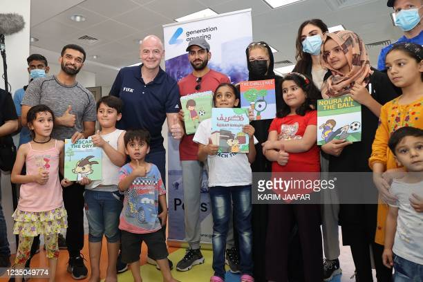 President Gianni Infantino poses for a picture with young Afghan refugees at their place of accommodation at Park View Villas, a Qatar's 2022 FIFA...