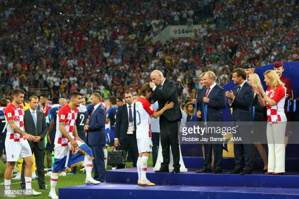 President Gianni Infantino presents Luka Modric of Croatia with his losers medal as Russia's President Vladimir Putin and France's President Emmanuel...