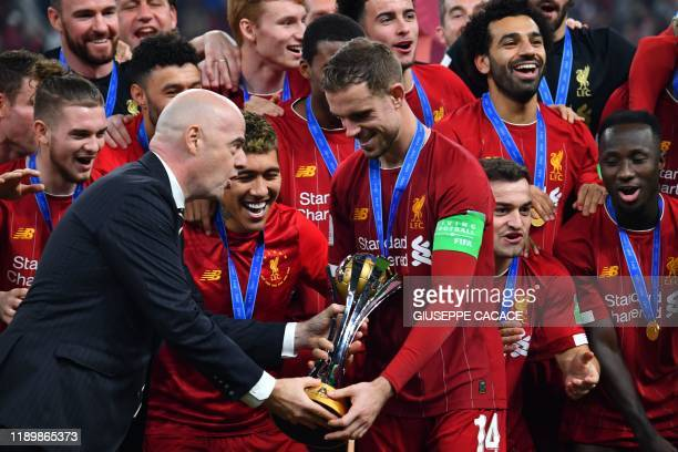 President Gianni Infantino presents the winner's trophy to Liverpool's English midfielder Jordan Henderson following the 2019 FIFA Club World Cup...