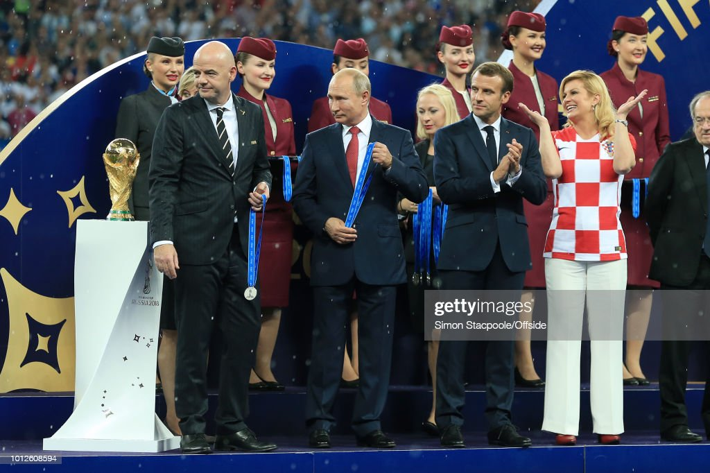 President Gianni Infantino (L), Russian President Vladimir Putin (2L), French President Emmanuel Macron (2R) and Croatian President Kolinda Grabar-Kitarovic stand on stage in the rain during the presentations after the 2018 FIFA World Cup Russia Final between France and Croatia at the Luzhniki Stadium on July 15, 2018 in Moscow, Russia.
