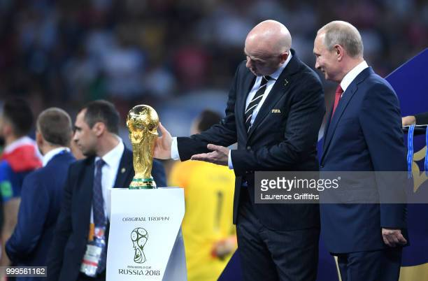 President Gianni Infantino shows the World Cup trophy to President of Russia Vladimir Putin following the 2018 FIFA World Cup Final between France...