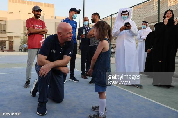 President Gianni Infantino speaks with a young Afghan refugee at their place of accommodation at Park View Villas, a Qatar's 2022 FIFA World Cup...