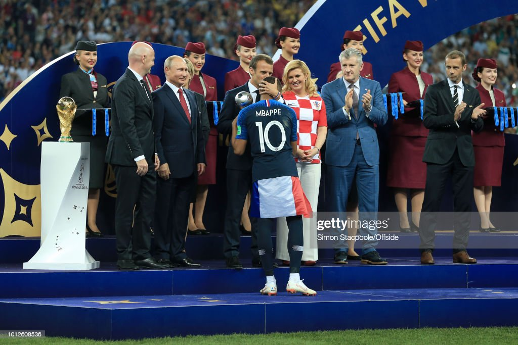 President Gianni Infantino (L) stands on stage next to the trophy alongside Russian President Vladimir Putin (2L), Croatian President Kolinda Grabar-Kitarovic (2R) and former Croatia player Davor Suker (R) as Kylian Mbappe of France is kissed on the head by French President Emmanuel Macron as he receives the Best Young Player of the Tournament Award during the presentations after the 2018 FIFA World Cup Russia Final between France and Croatia at the Luzhniki Stadium on July 15, 2018 in Moscow, Russia.