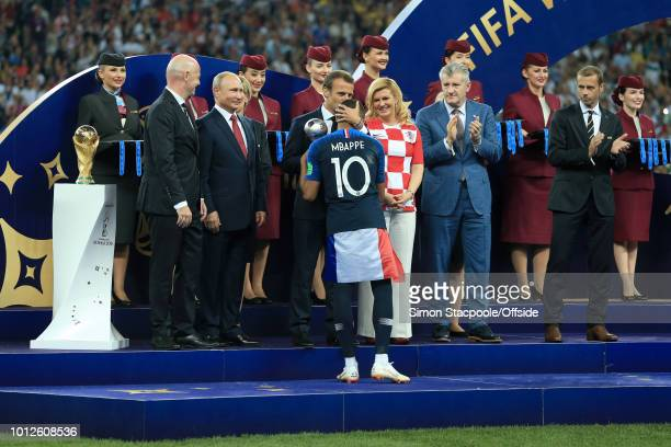 President Gianni Infantino stands on stage next to the trophy alongside Russian President Vladimir Putin Croatian President Kolinda GrabarKitarovic...