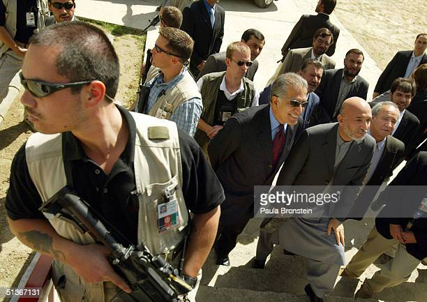 President Hamid Karzai and US Ambassador Zalmay Khalilzad take a question from the media as US security stands guard after attending a ceremony at...