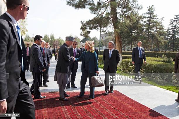 President Hamid Karzai of Afghanistan greets Secretary of State Hillary Rodham Clinton on October 20, 2011 outside the Presidential Palace in Kabul,...