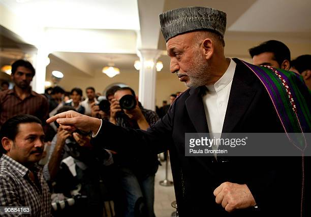 President Hamid Karzai points as he speaks to the media for the first time since full preliminary results were announced at the Presidential palace...