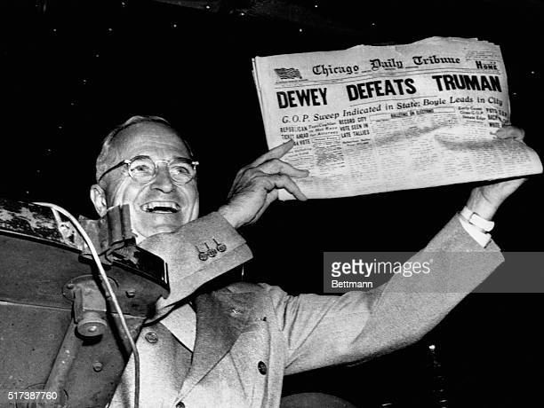 President Harry S Truman gleefully displays a premature early edition of the Chicago Daily Tribune from his train in St Louis Missouri after his...