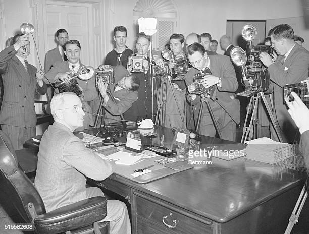 President Harry S. Truman poses at his desk for a group of White House photographers.
